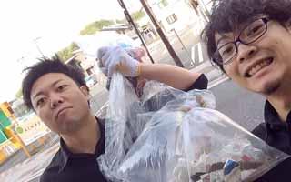 街路樹の下にあるゴミを拾う男性